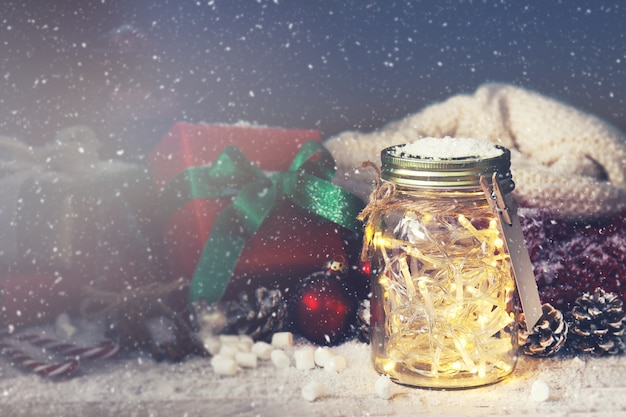 Crystal jar with lights with a gift next to it while it snows