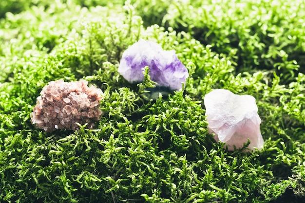 美しい苔の背景に結晶鉱物石。儀式、瞑想、精神修養のための魔法の石。ソフトフォーカス。