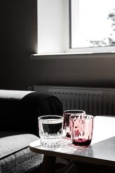 흰색 테이블에 크리스탈 레드 유리입니다. 햇빛에 단단한 그림자.