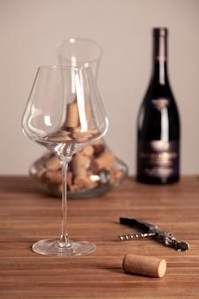Crystal red wine glass, bottle, corkscrew, transparent decanter, corks on wooden table