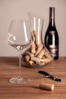 Crystal red wine glasse, bottle, corkscrew, decanter with corks on wooden table