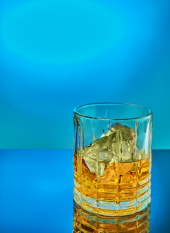 Crystal round glass of scotch whiskey or brandy on a blue gradient background with reflection.