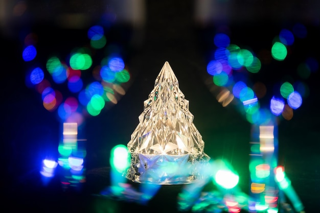 A crystal shining christmas tree stands behind two wine glasses in blur surrounded by a shining