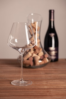 Crystal shiny glass, bottle of red wine, transparent decanter filled with corks on wooden table.