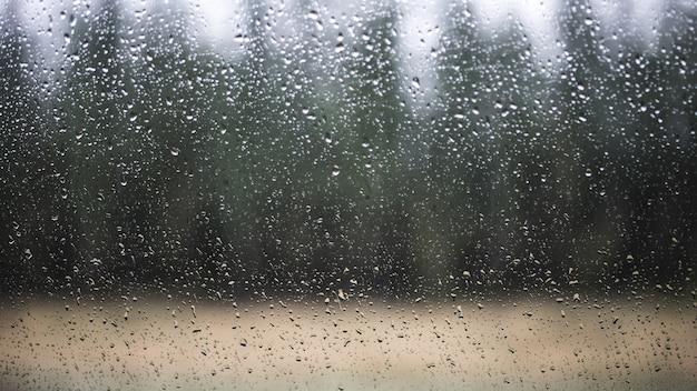 Finestra di cristallo con gocce d'acqua nel paesaggio della natura