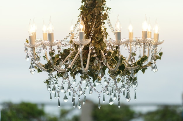 Crystals hang from the chandelier decorated with greenery