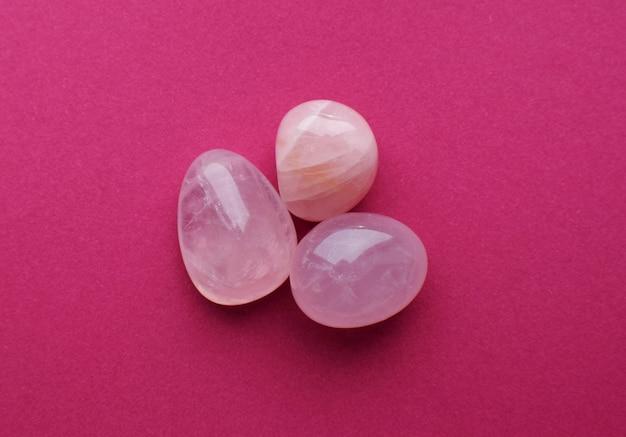 밝은 분홍색 배경에 장미 석영의 결정입니다. 아름다운 준보석