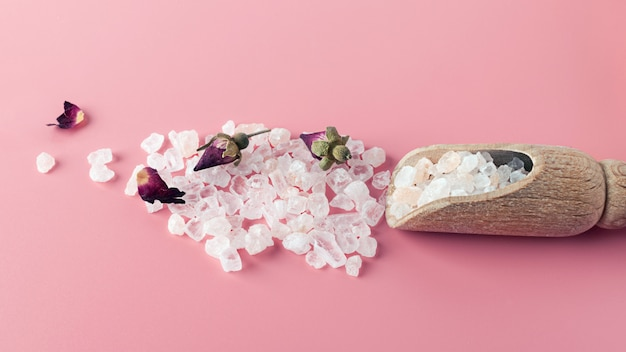 Crystals of salt for spa and bath are scattered on a pink background with copy space. essential oil with rose petals and buds. the concept of alternative medicine, relaxation, body breathing. eco.