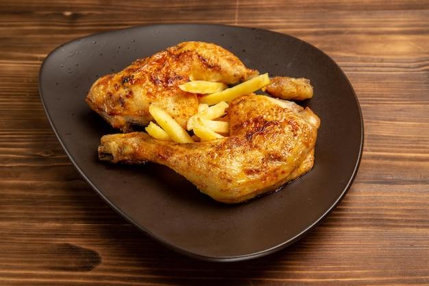 テーブルの上のフライドポテトと鶏の脚を食欲をそそる鶏の脚をクローズアップ