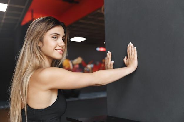 黒い壁に寄りかかっているcsportswomanは少し喜んで笑顔で横向きになります。