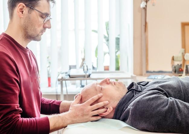 Cst 치료사는 부드러운 터치를 사용하여 남성 환자 정골의 두개골 관절 관절을 촉진하고 수동 요법을 사용합니다.