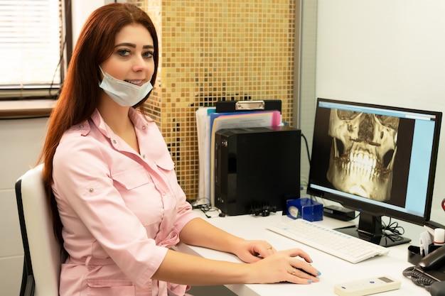 女性歯科医の医師は、顎のctスキャンコンピューターのテーブルに座っています。医者はプロの服を着ています。