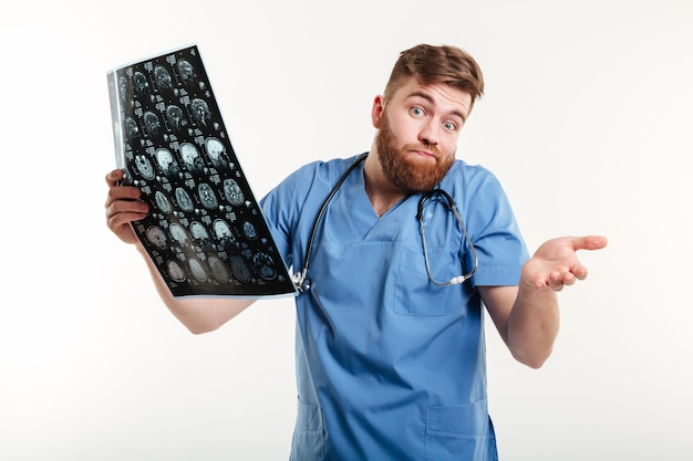 Ctスキャンを保持している欲求不満の有用な医師の肖像画