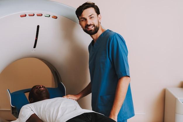 肯定的な医師がctスキャナーアフロ患者を起動します。
