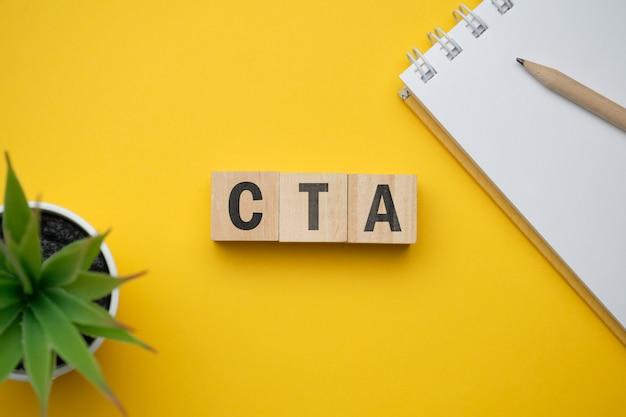 最新のマーケティング流行語-ctaの行動を促すフレーズ。ブロックと木製のテーブルの上から見る。上面図。