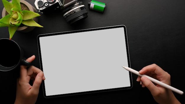 Ctop вид женские руки, держащие стилус, планшет, макет камеры, кофейный завод на черном фоне