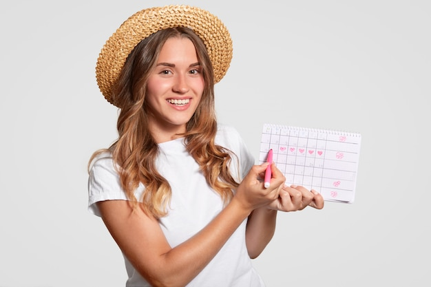 Cuacasian woman has charming smile, holds periods calendar, marks with marker day of starting menstruation