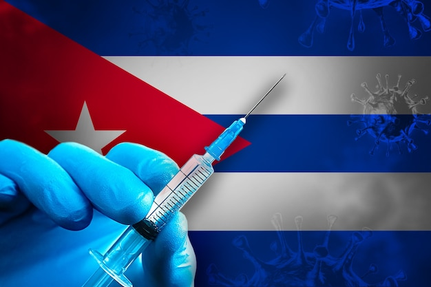 Cuba covid19 vaccination campaign hand in a blue rubber glove holds syringe in front of flag