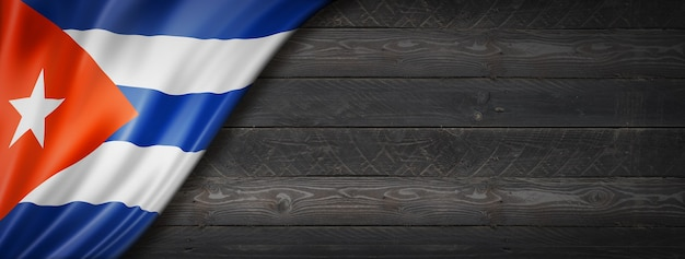 Cuba flag on black wood wall. horizontal panoramic banner.