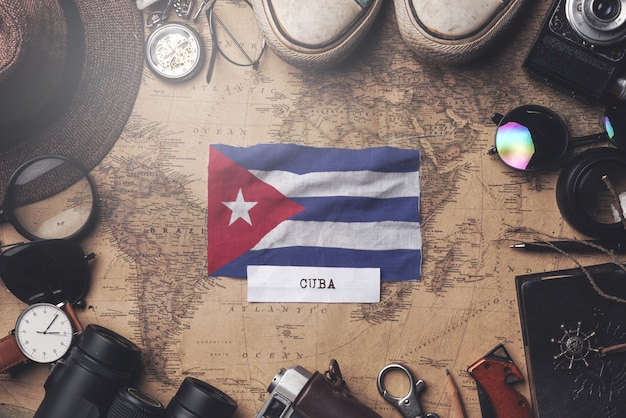 Cuba flag between traveler's accessories on old vintage map. overhead shot
