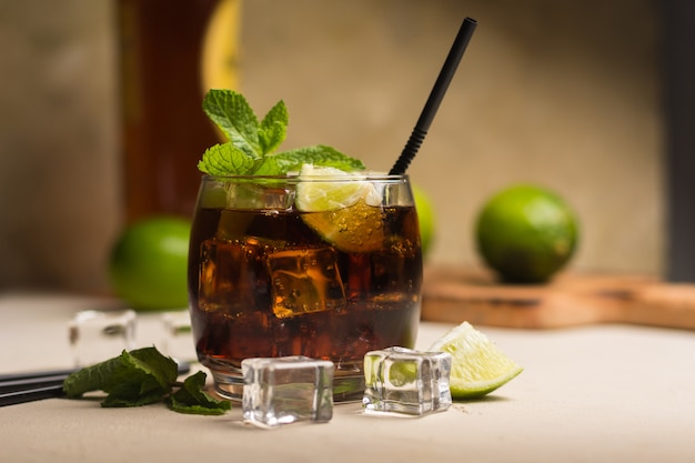 Cuba libre drink with mint leaves and pieces of lime.