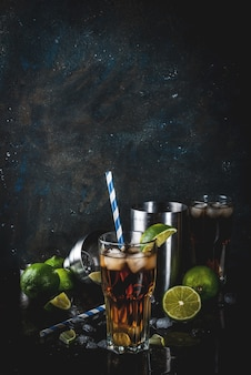Cuba libre, long island or iced tea cocktail with strong alcohol, cola, lime and ice, two glass, dark surface copy space