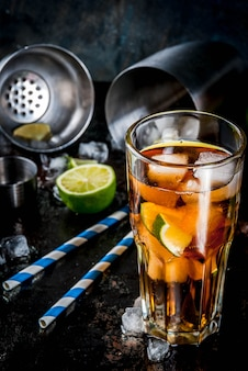 Cuba libre, long island or iced tea cocktail with strong alcohol, cola, lime and ice