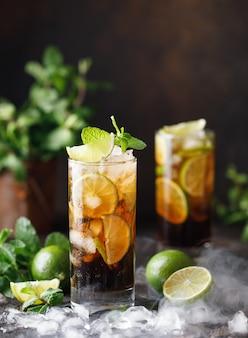 茶色のラム酒、コーラ、ミント、ライムのキューバリブレ。キューバリブレまたはロングアイランドアイスティーカクテルと濃い飲み物