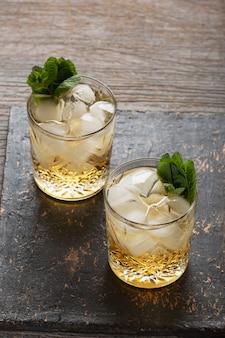 Бокал рома на деревянном фоне, cuba libre или коктейль со льдом на лонг-айленде с крепкими напитками