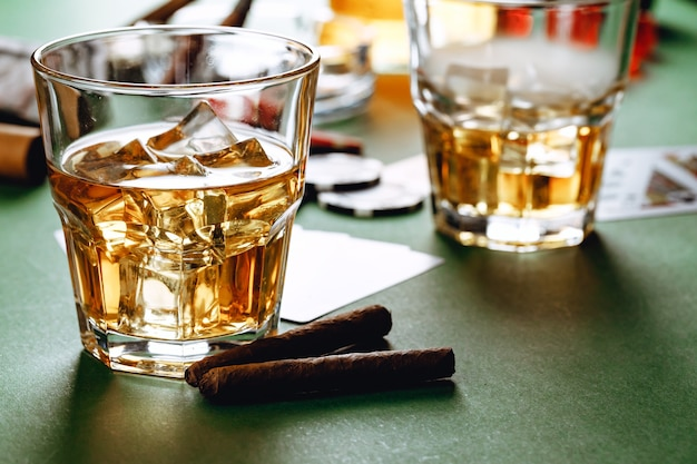 Cuban cigar whiskey glass and chips on table