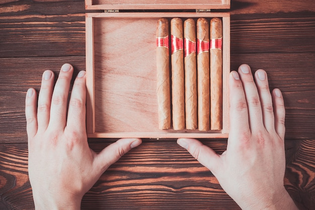 Cuban cigars in a box in male hands on a wooden background