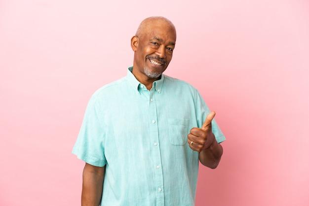 엄지손가락 제스처를 주는 분홍색 배경에 고립 된 쿠바 수석