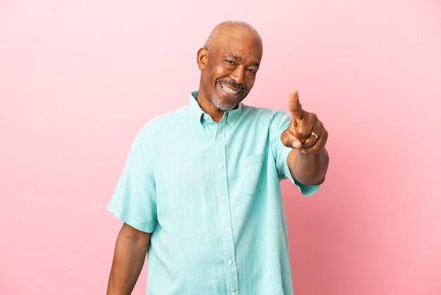 Кубинский старший изолирован на розовом фоне, указывая вперед с счастливым выражением лица