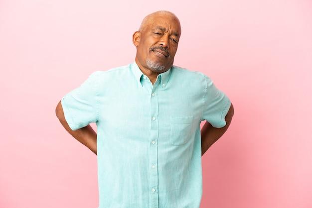 Кубинский старший изолирован на розовом фоне страдает от боли в спине из-за того, что приложил усилие