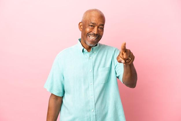 Кубинский старший изолирован на розовом фоне удивлен и указывая вперед