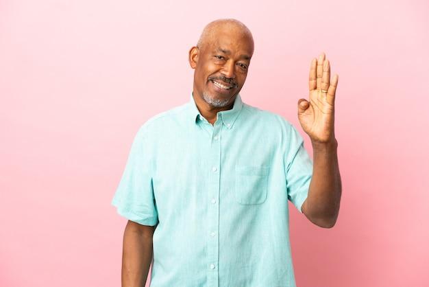 Кубинский старший изолирован на розовой стене, салютуя рукой со счастливым выражением лица