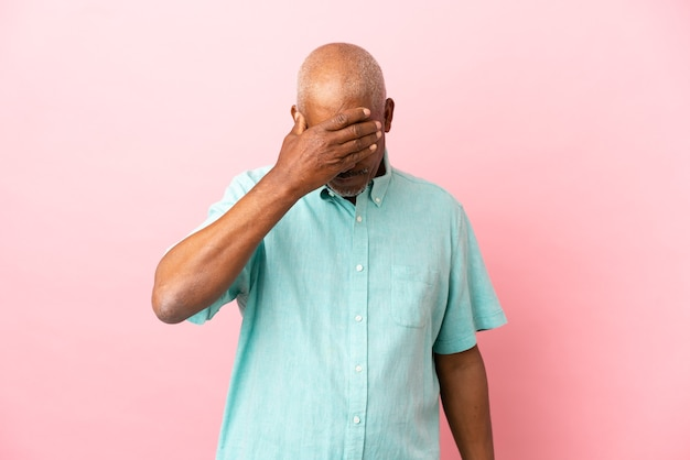 Cuban senior isolated on pink background covering eyes by hands. do not want to see something