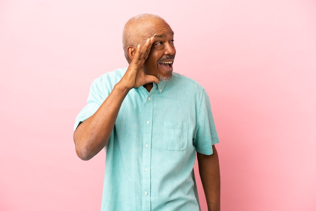 Cuban senior isolated on pink background shouting with mouth wide open to the side
