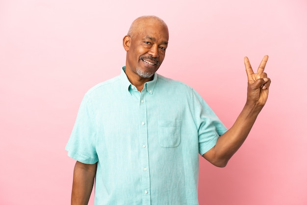 Cuban senior isolated on pink background smiling and showing victory sign