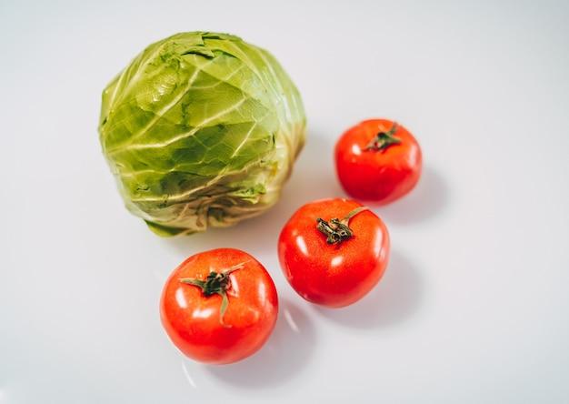 Cubbage и помидоры на белом фоне. концепция органических продуктов питания. оставаться здоровым. потребление свежих продуктов.