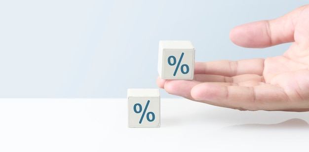 Cube block in hand with percent sign