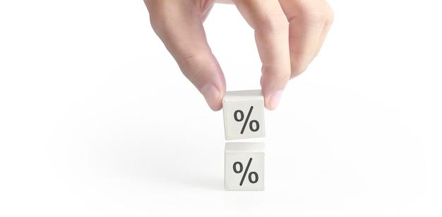 Кубик блок в руке с иконой процентов