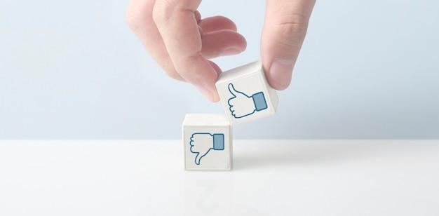 好き嫌いのシンボルが付いたキューブブロックを手に。親指を上に、親指を下に