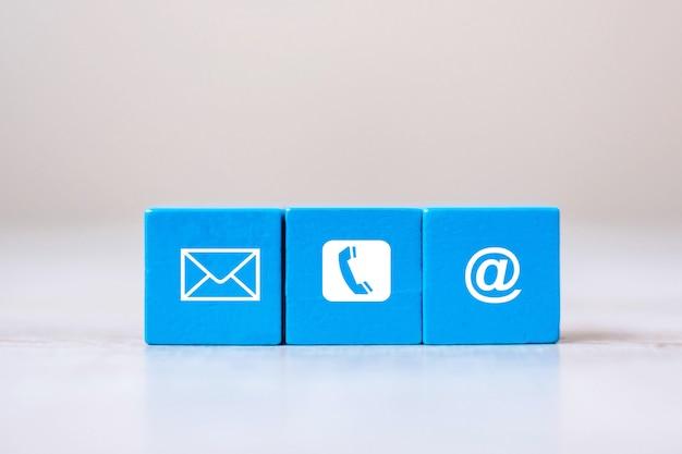 Кубический блок с символом электронной почты, телефона и адреса веб-сайта на фоне стола