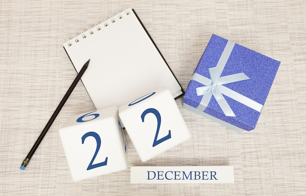 Cube calendar for december 22 and gift box, near a notebook with a pencil