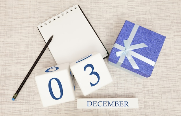 Cube calendar for december 3 and gift box, near a notebook with a pencil