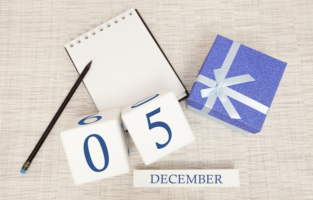 Cube calendar for december 5 and gift box, near a notebook with a pencil