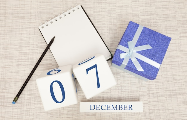 Cube calendar for december 7 and gift box, near a notebook with a pencil