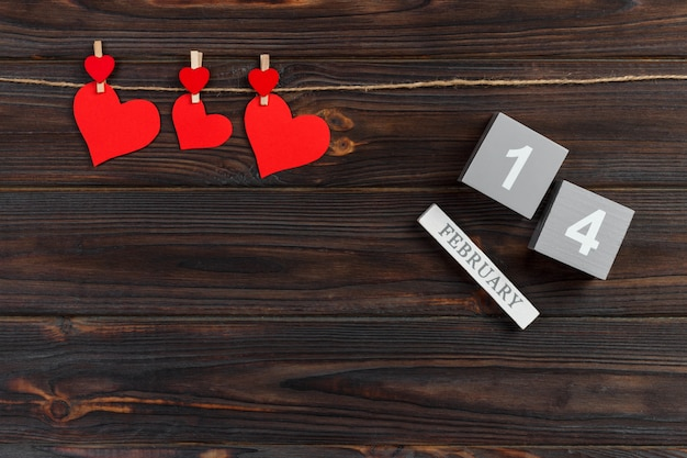 Cube calendar with red hearts on wooden table