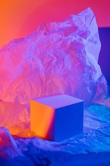 ネオンの光の中でしわくちゃの紙で表彰台を立方体。製品を表示するスタイリッシュな幾何学的形状。抽象的な背景